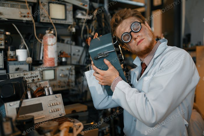 Scientist in glasses holds electrical device