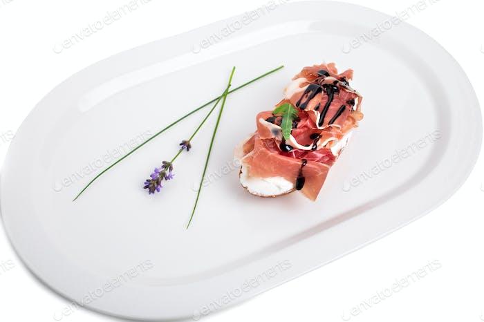 Prosciutto bruschetta with ricotta and arugula.