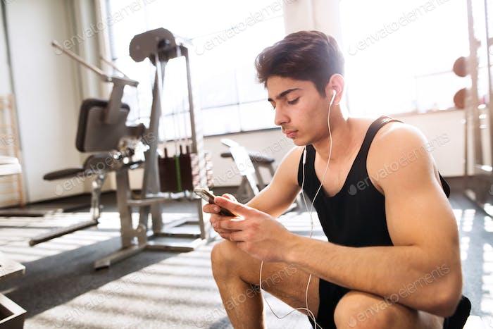 Hispanic man in gym resting, holding smart phone, listening music