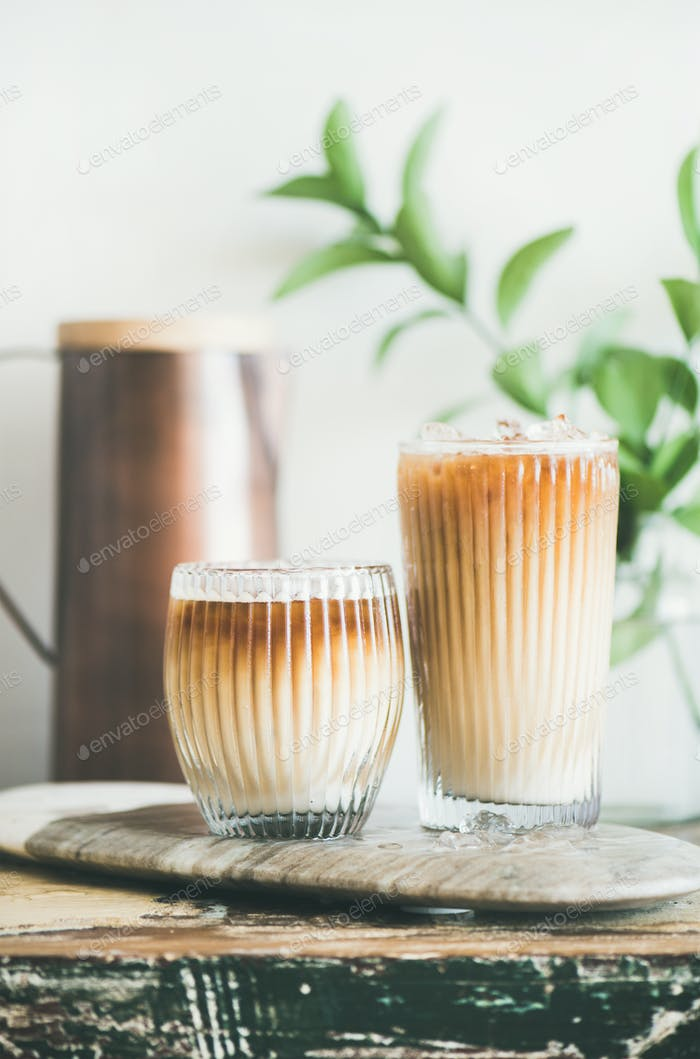 Iced coffee drink in tall glasses with milk, close-up