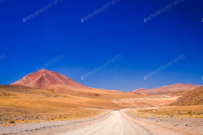 Sandy and gravel desert road through Altiplano