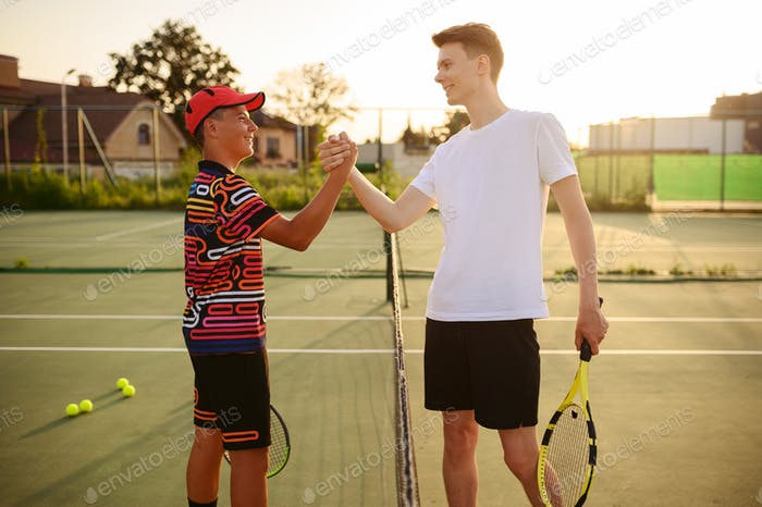 Tennis players with rackets shake hands at the net