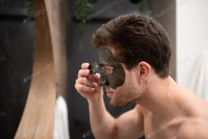 Glad man applying mud mask in bathroom