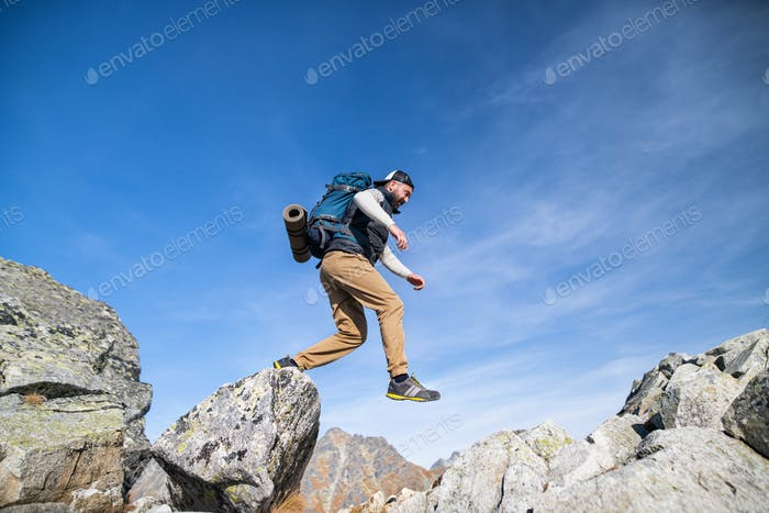 Mature man with backpack hiking in mountains in summer