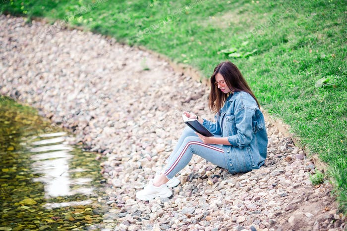 Relaxed young woman reading book in park