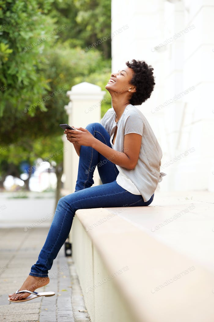 Happy young woman with mobile phone sitting by a street
