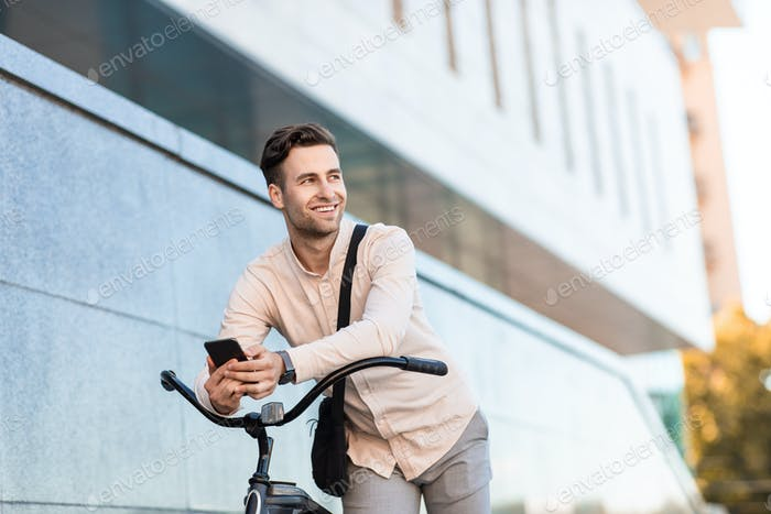 Cheerful man poses with bicycle. Young hipster with smartphone near building