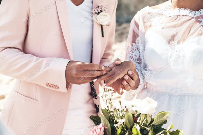 Groom in pink jacket wears ring on the finger of the bride on the beach