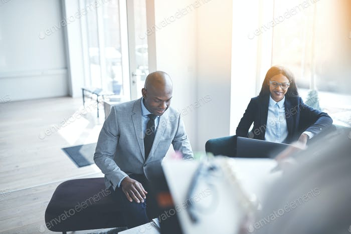 Smiling African American businesspeople meeting with colleagues in an office