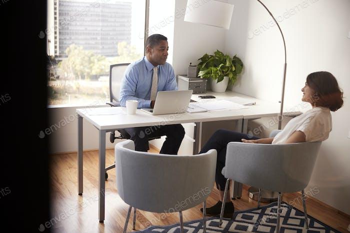 Male Financial Advisor In Modern Office Sitzen Am Schreibtisch Treffen Weibliche Klientin