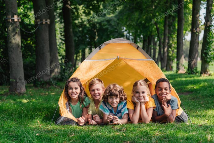 happy multicultural kids smiling while lying near camp