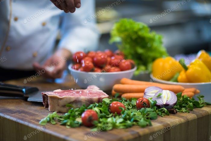 Chef setzen Salz auf saftige Scheibe rohes Steak
