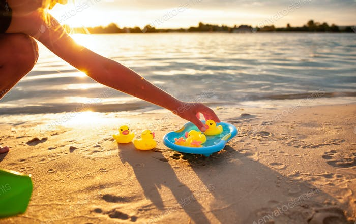 Unrecognizable kid playing with rubber ducks on seashore