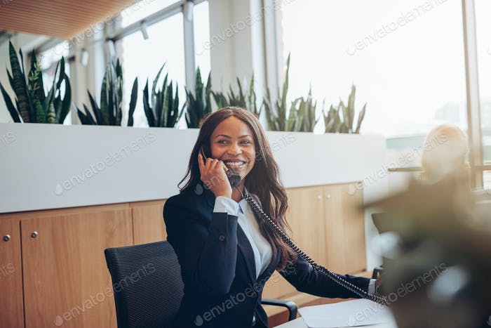 Smiling African American businesswoman talking on the phone at work