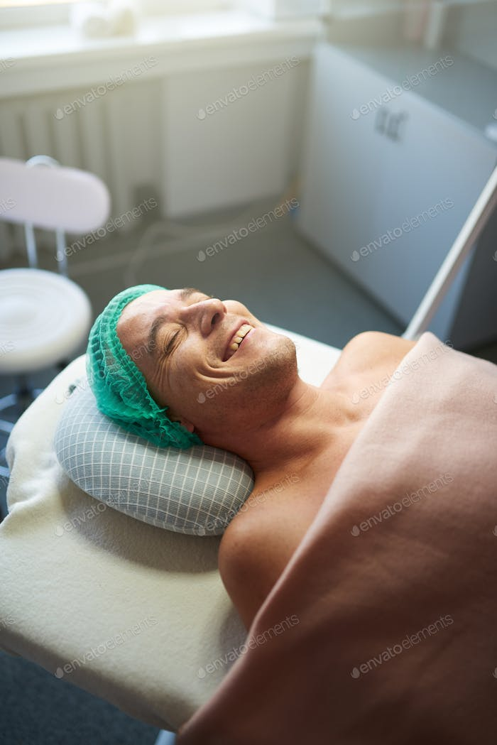 Smiling client lying in cosmetological cabinet