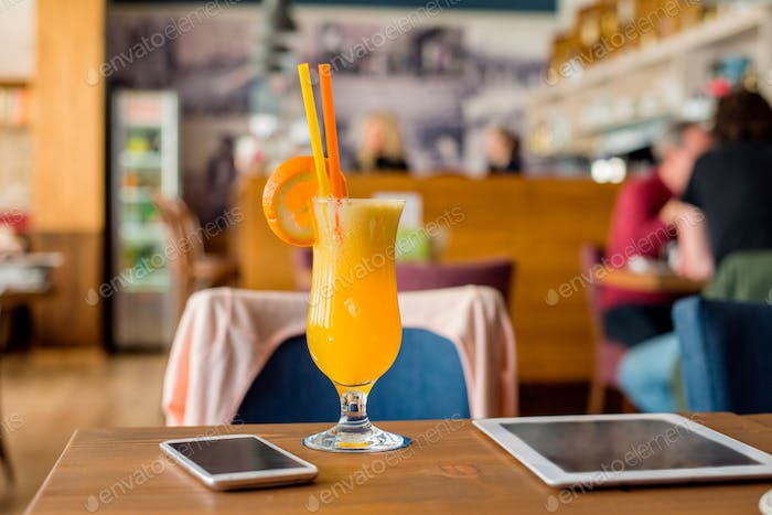 Orange drink, tablet, smartphone laid on table in cafe