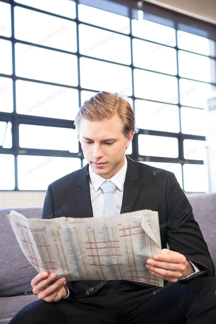 Businessman reading a newspaper in office