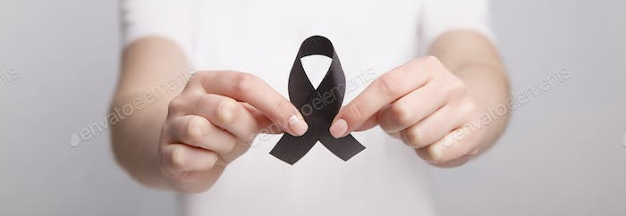 Black Awareness Realistic Ribbon in hands, support, hope