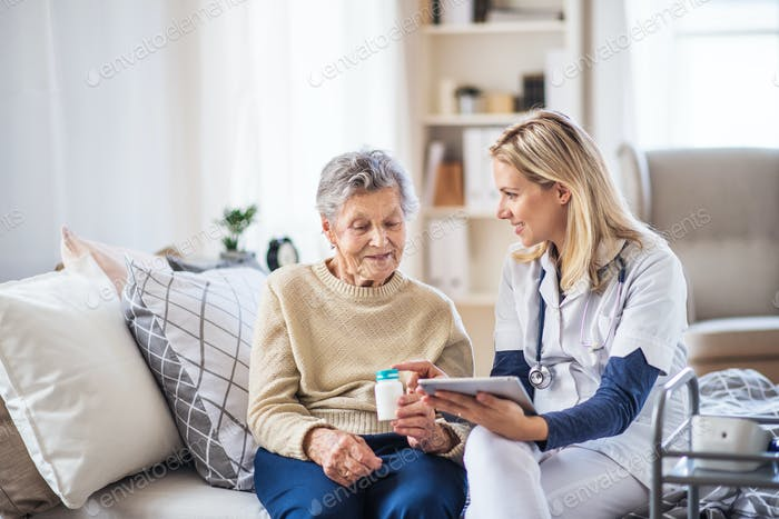 A health visitor with tablet explaining a senior woman in how to take pills.