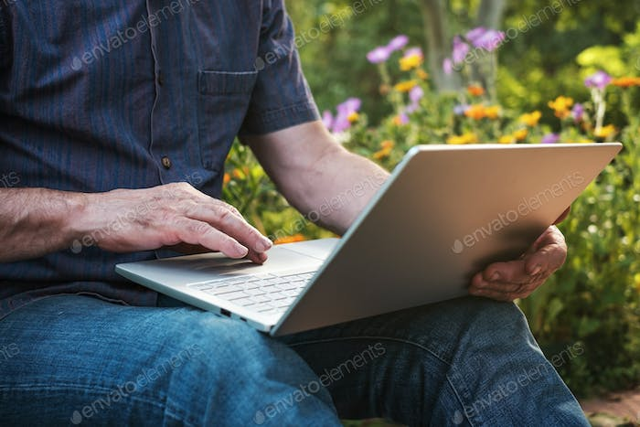 Cropped image of a mature man working on his laptop in garden, old male blogger typing on notebook