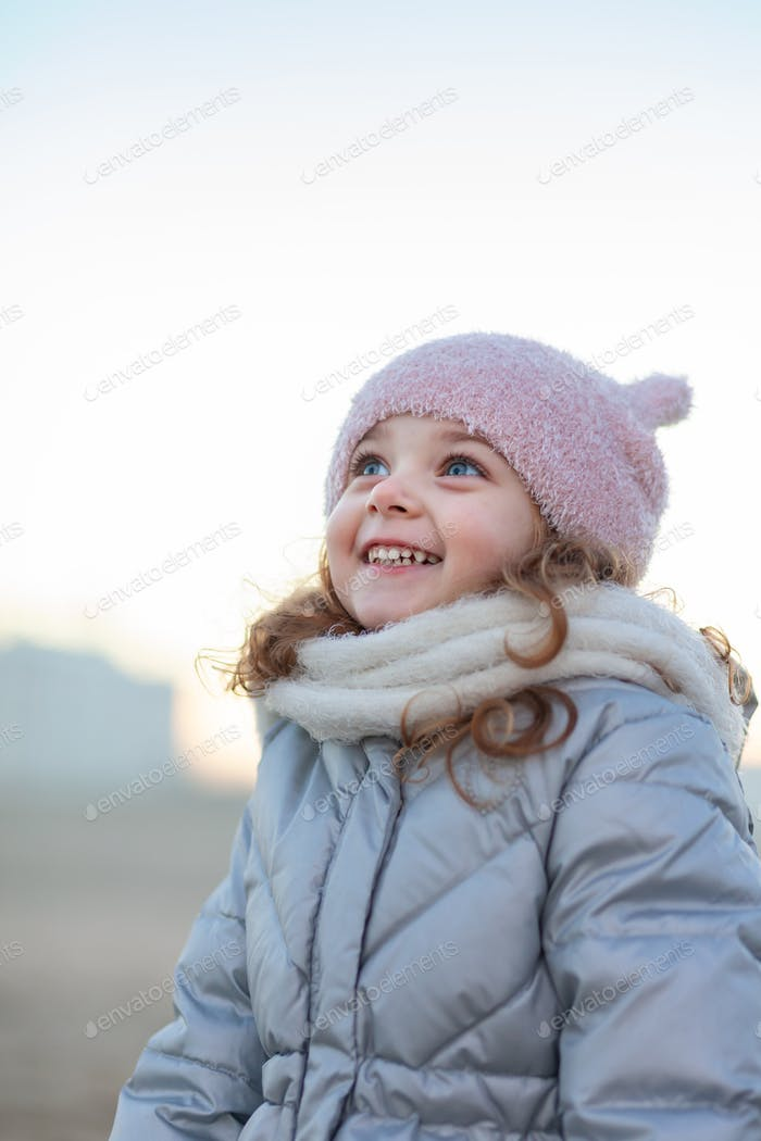 Adorable little girl smiles and looks at the sky.