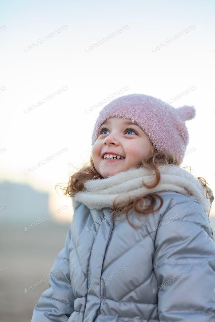 Entzückendes kleines Mädchen lächelt und schaut in den Himmel.