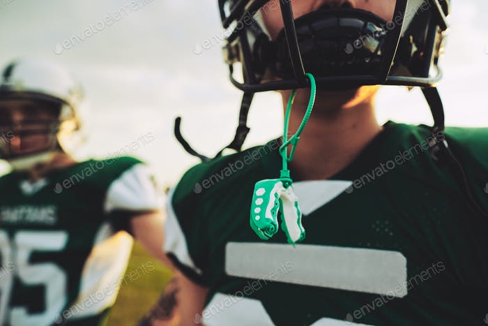 Young American football player with his mouthguard out during practice