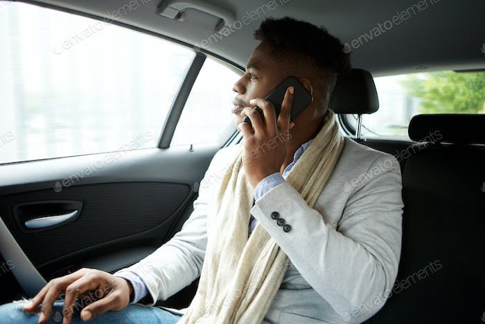 young businessman talking with mobile phone while in backseat of car