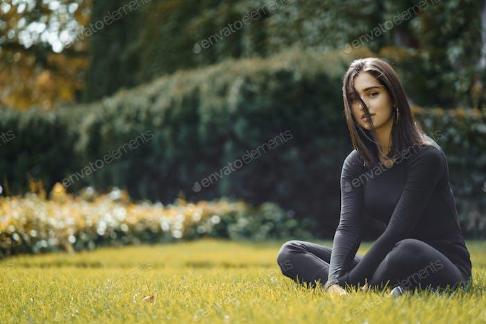 morena chica caminando a través del Parque durante otoño