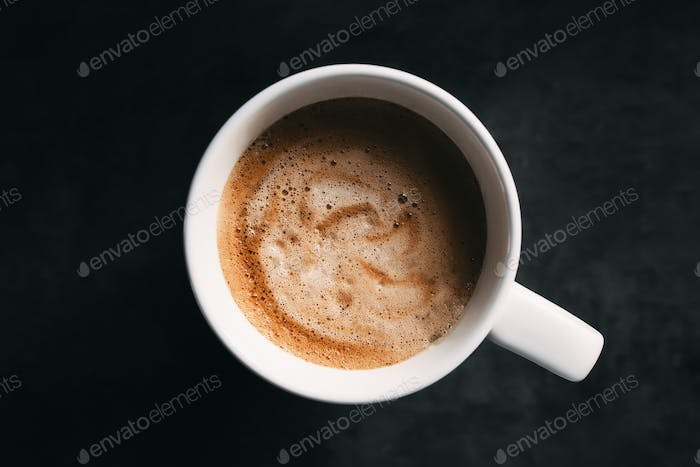 White coffee cup on the dark gray background