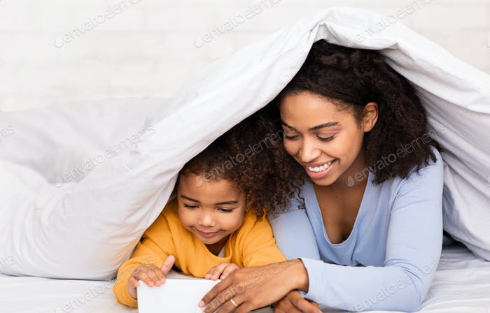 Mother And Daughter Using Cellphone Watching Cartoons In Bed Indoors