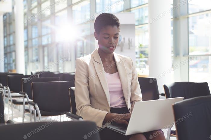 Front view of African American businesswoman sitting on chair and using laptop in lobby at office