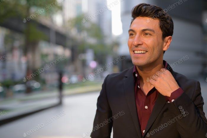 Gesicht der jungen glücklichen hispanischen Geschäftsmann denken außerhalb des Bürogebäudes
