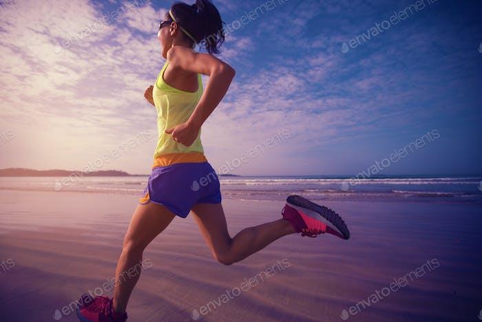 Woman runner morning exercise on sunrise beach