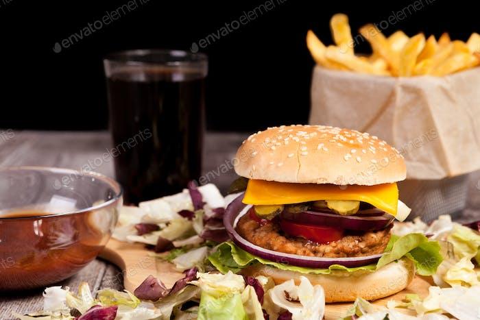 Hausgemachter Burger auf Holzplatte neben Pommes, Cola und Ketchup
