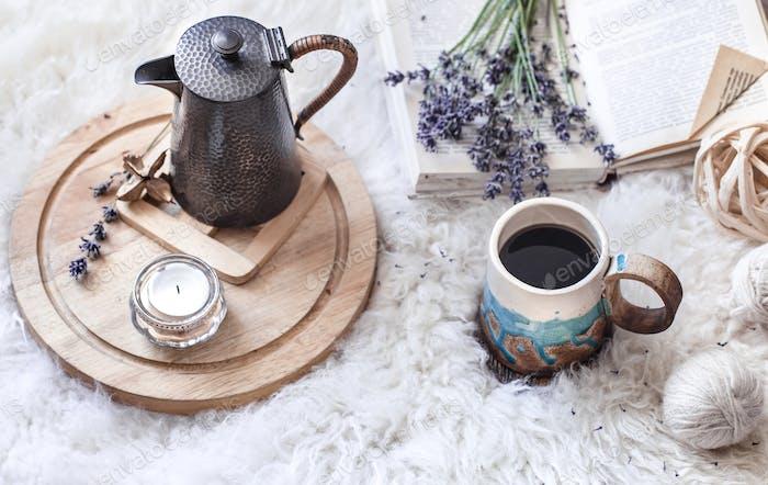 Gemütliches Stillleben mit einem Wasserkocher und einer Tasse heißem Getränk