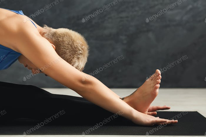 Unrecognizable fitness woman stretching at grey background indoors