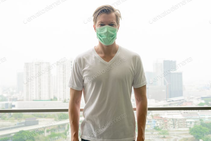 Young man wearing mask for protection from corona virus outbreak and pollution from the city