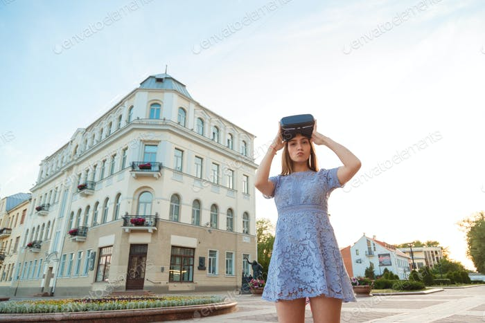 Young Woman in summer dress with VR device outdoor.