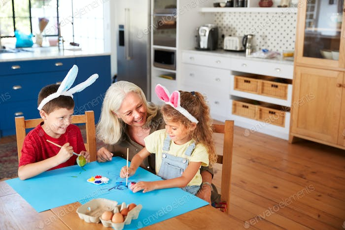 Grandmother With Grandchildren Wearing Rabbit Ears Decorating Easter Eggs At Home Together