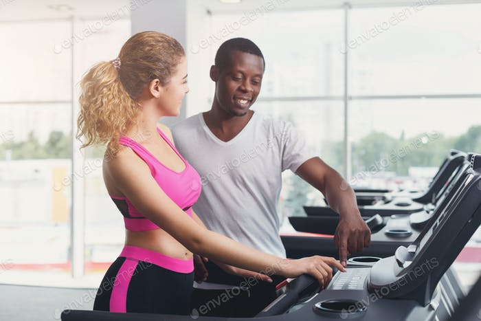 Fitness instructor helps young woman on treadmill