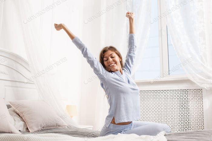 Happy brunette girl in the light-blue pajama stretches her arms up sitting on the canopy bed next to