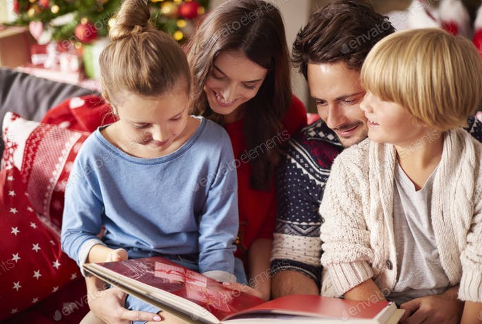 Family reading book at Christmas