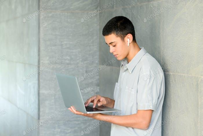 Junger Mann mit einem Handheld-Laptop