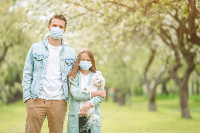 Family of father and daughter in blooming cherry garden in masks