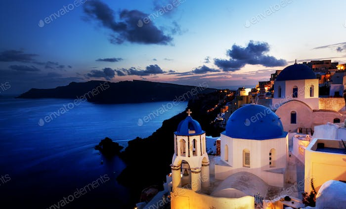 Oia town on Santorini island, Greece at night. Rocks on Aegean sea.