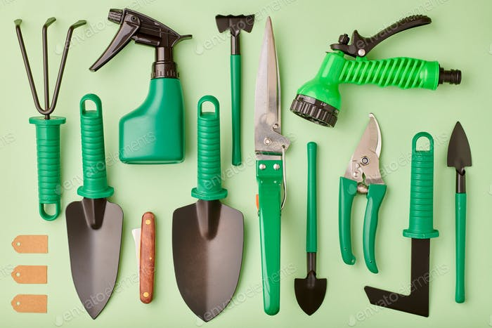 Gardening tools on green background flat lay