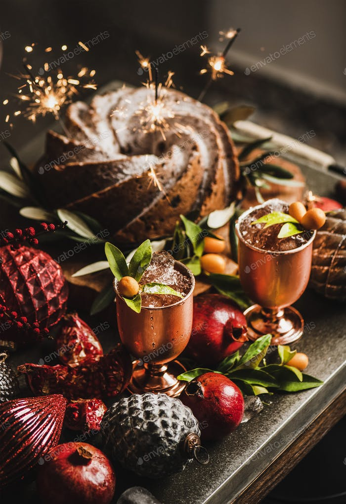 Christmas bundt cake with sparklers and citrus cocktails in goblets