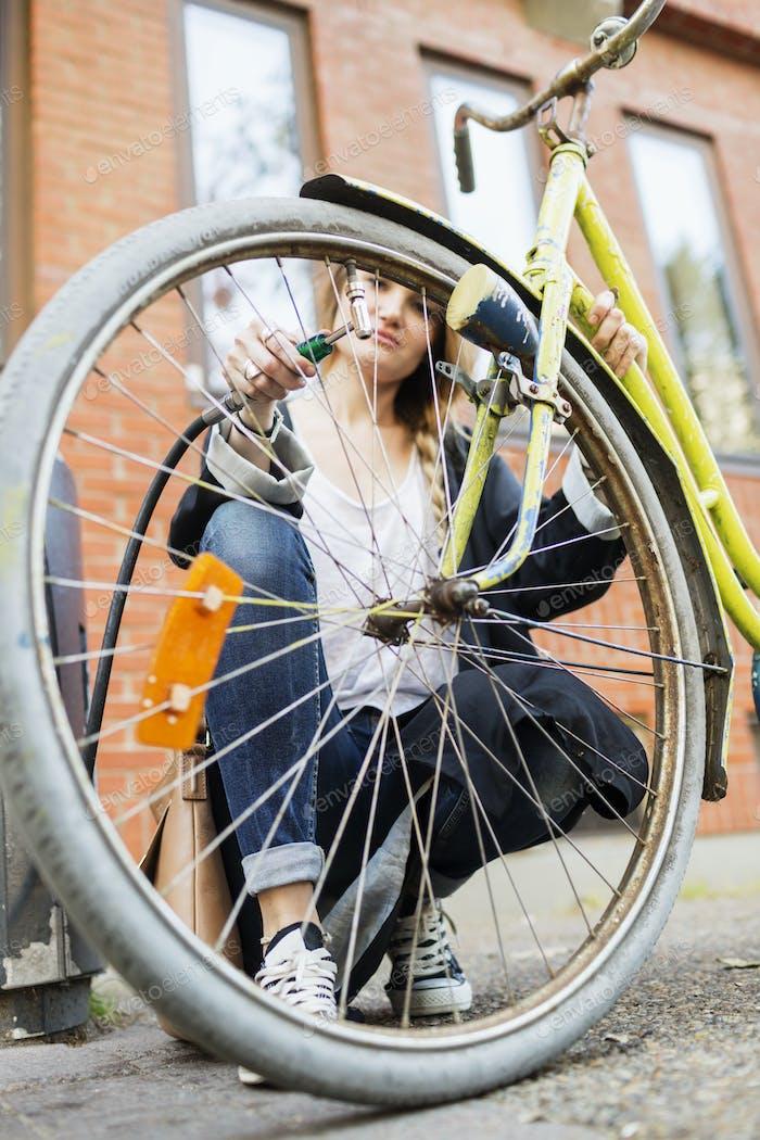 Woman inflating bicycle tire on sidewalk