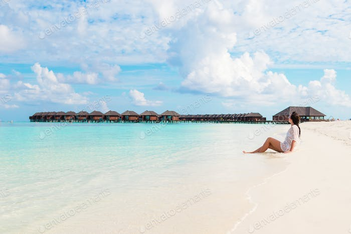 Young beautiful woman relaxing on beach during tropical vacation